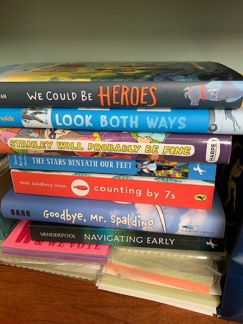 stack of books, including We Could Be Heroes