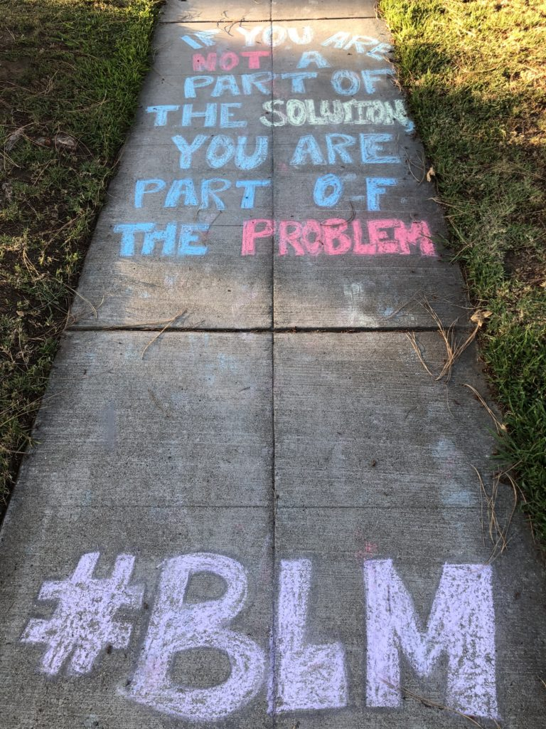 """Chalk art reads """"If you are not part of the solution you are part of the problem #BLM"""